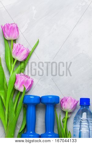 Spring Flatlay Sports Composition With Blue Dumbbells And Purple Tulips.