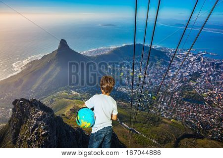 Travel to Africa. Panorama Cape Town, photographed from  cableway cabin. The concept of active tourism and recreation. The boy with the globe in hands standing on top of Table Mountain