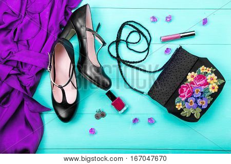 spring clothes women's clothes - a purple dress embroidered bag black heels earrings nail polish lipstick. turquoise wooden background top view