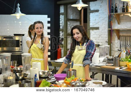 Two young happy female friends cooking and talking in the kitchen. Cooking class.