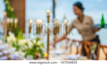 Blurred of Table in the Restaurant witch candles and woment servant on the Beach, Bali. Swirl Bokeh