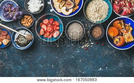 Ingredients for healthy breakfast over dark blue background, top view, copy space. Fresh and dried fruit, chia seeds, oatmeal, nuts, honey. Clean eating, vegan, healthy food, detox, dieting concept