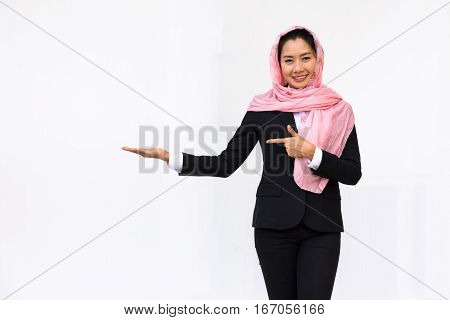 Empty hand holding of smiling woman in black suit wearing pink turban on white background.