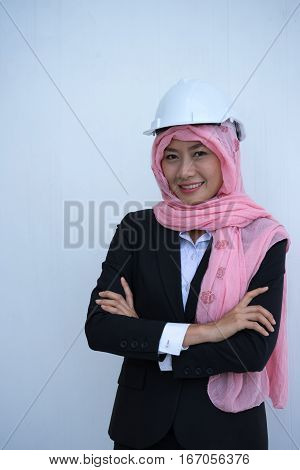 Female engineers smiling in black suit with hat and wearing pink turban standing arms crossed on white background.