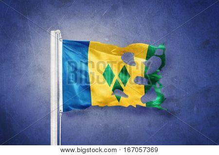 Torn flag of Saint Vincent and the Grenadines flying against grunge background