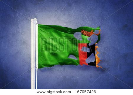 Torn flag of Zambia flying against grunge background