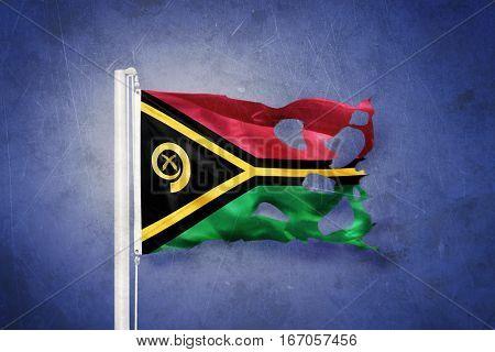 Torn flag of Vanuatu flying against grunge background