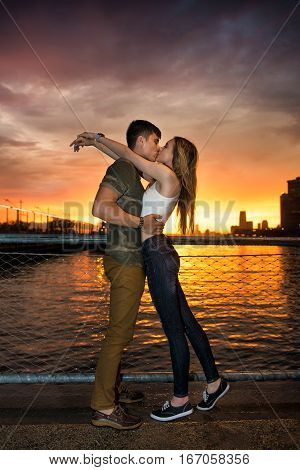 Yound beautiful couple in love kissing near the ocean pier in city at sunsnet time