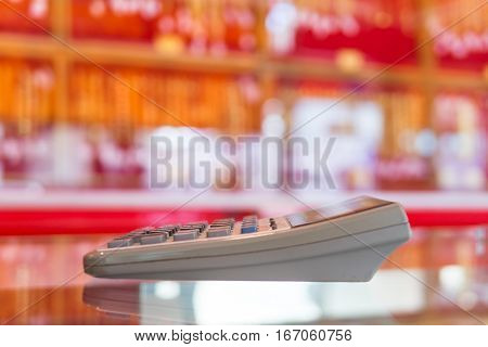 Old big calculator on the mirror in red shop blurr background