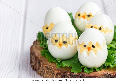 Little chicken in nest deviled eggs served with salad on wooden board horizontal copy space