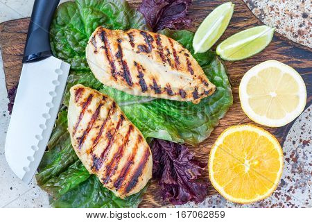 Grilled chicken breast in citrus marinade on salad leaves and wooden cutting board horizontal top view