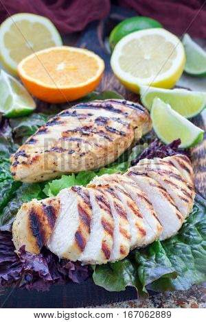 Grilled chicken breast in citrus marinade on salad leaves and wooden cutting board vertical