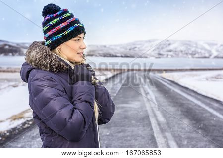 Portrait of a nice woman on winter road, wearing warm coat and stylish hat, enjoying cold Scandinavian weather, extreme winter holidays, Iceland