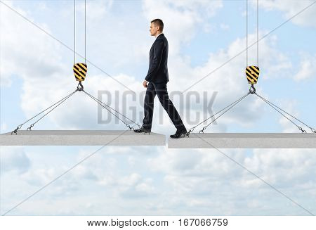 Businessman is stepping over a gap from one concrete panel to another in the air on the background of the sky. Goals and aspirations. Business activity. Risk