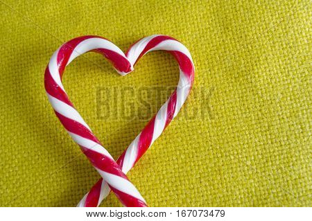 Peppermint Candy Canes in Heart Shape on textile background.