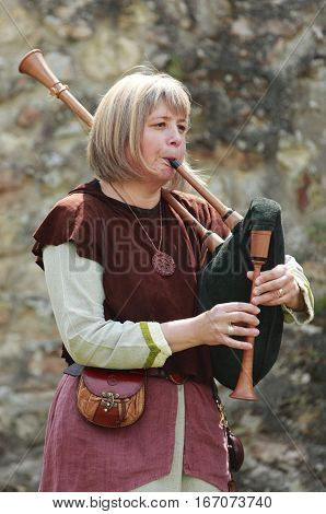 Nogent le Rotrou,France-May16th,2010:A woman wearing traditional medieval clothes play a bagpipe during the