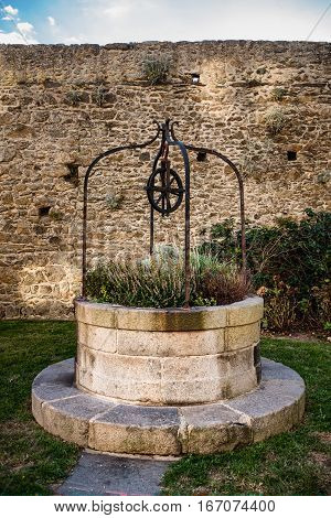 Decorative stone well with flowers and wheel in Saint-Malo, Bretagne France