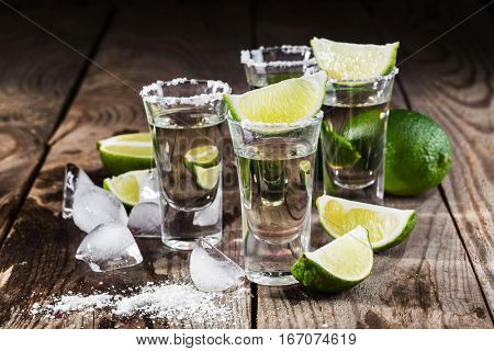 Mexican tequila gold in short glasses with salt, lime slices and ice on a wooden table