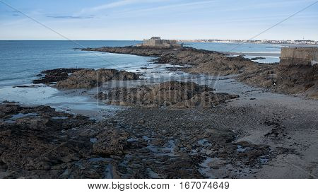 Bare rocks on sandy beach in Saint-Malo, Bretagne France