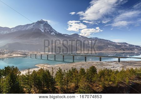Pont de Savines with Serre-Poncon lake and the Grand Morgon on an early winter morning. Savines-le-Lac Hautes-Alpes Southern French Alps. France