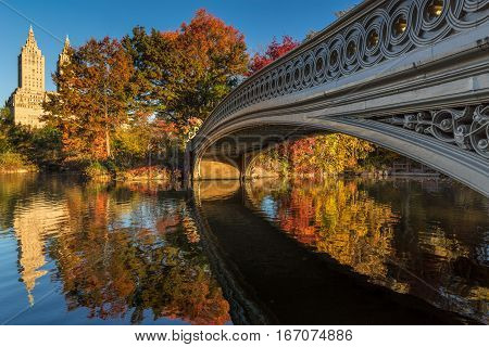 Fall in Central Park at The Lake with the Bow Bridge. Morning view with colorful Autumn foliage on the Upper West Side. Manhattan New York City