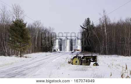 Rigaud, Quebec, March 5, 2016 -- Three silver silos on a snowy landscape with an old tractor displayed on the snow covered field in front near rural Rigaud, Quebec, on a slightly overcast but bright day in March.