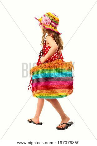 Little girl is dressed in red summer dress, beach shoes, sunglasses and hat. She is having a bright beach bag. She is going to go on a beach.