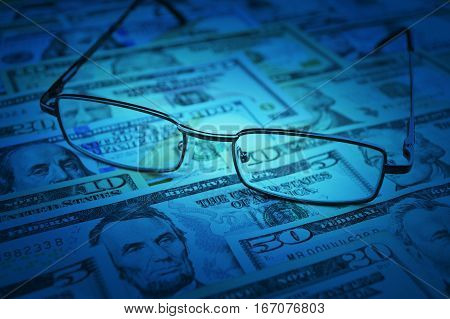 Glasses on dollar money blue tone Business financial concept