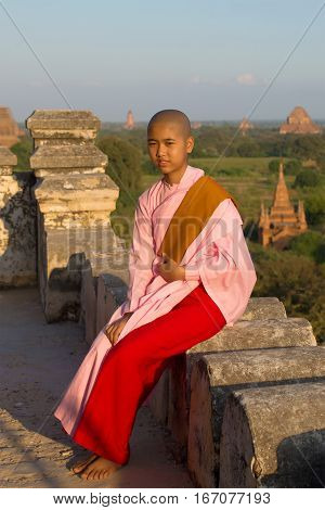 BAGAN, MYANMAR - DECEMBER 24, 2016: Burmese girl-a nun is sitting on a background of ancient Buddhist temples of Bagan