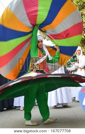 CAIRO, EGYPT, JANUARY 23 2016: The whirling dervish of Al Tannoura Folklore Troupe, Cairo, Egypt during the  International Folklore Festival held in the city center.