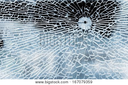 Broken glass with bullet hole and cracks