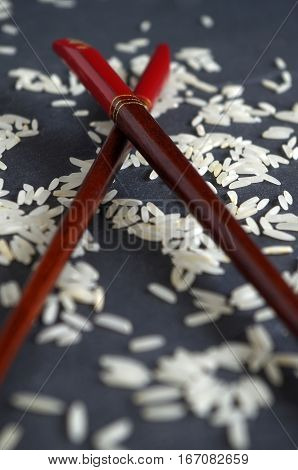 crude grains of rice with chinese chopsticks