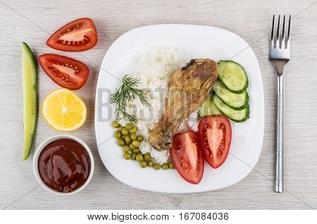 Fried Legs With Rice, Pieces Of Tomatoes And Cucumbers, Lemons