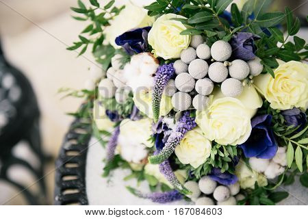 Bouquet of roses lying on the snow-covered table. The bouquet consists of yellow and purple flowers. The bouquet of flowers inserted cotton
