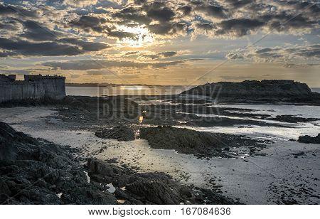 Dramatic sunset illumination of low tide ocean coast in Saint-Malo, Bretagne France