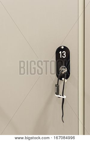 Grey Cabinets With Numbered Locks And Keys In School, Gym Or Locker Room