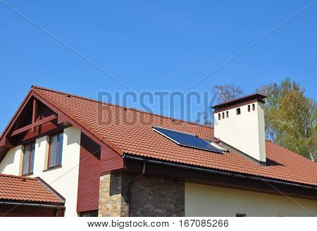 Energy Efficiency New Passive House Building Concept Exterior. Cozy house Roofing with Vacuum Solar Water Panel Heating Solar Panels Skylights Outdoor.