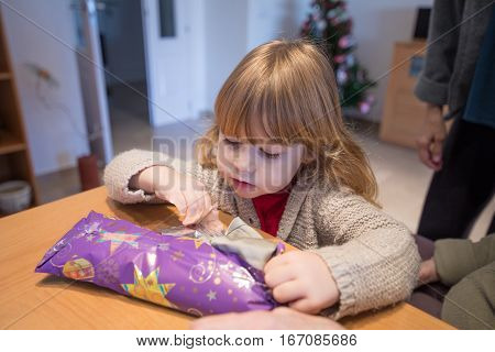Child Opening Christmas Present Wrapped In Paper
