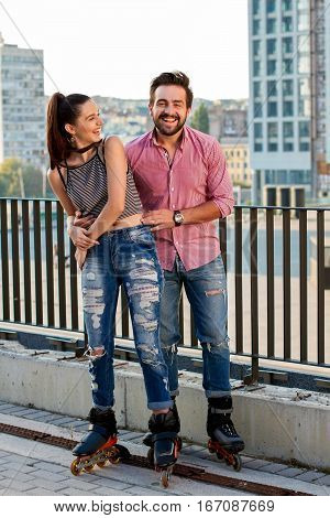 Couple on rollerblades laughing. Two people on urban background. Young, free and happy.