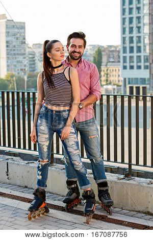 Man and woman on rollerblades. Couple on urban background. Enjoy the romance.