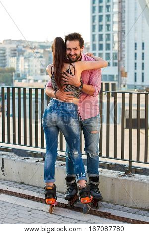 Couple on rollerblades is hugging. Smiling man on urban background. Find love in concrete jungle.