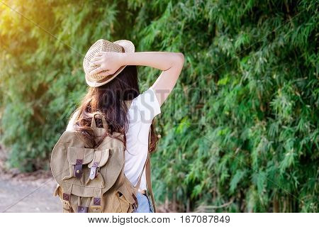Asian hipster cute teen girl with backpack enjoying sunset on peak. Tourist traveler on background valley landscape view mockup sunlight in trip in basque country