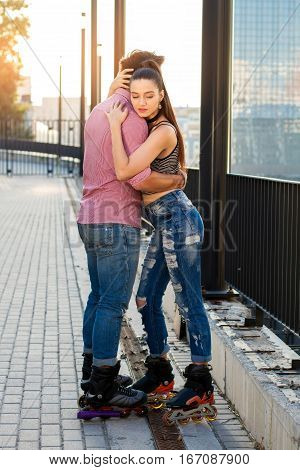 People on rollerblades hugging. Couple on city background. Hold me tighter.