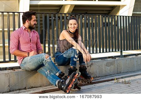 People on inline skates sitting. Young woman is smiling. Idea for active date.