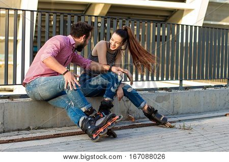 Couple on rollerblades is sitting. Young woman laughing. Great idea for first date.