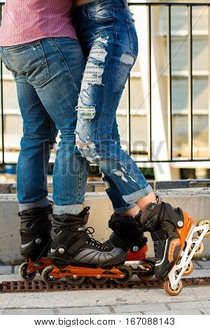 Legs of couple wearing rollerblades. Man with woman in jeans. Style and sport.
