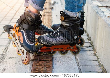 Feet on rollerblades. Orange and black inline skates. High durability and new design.
