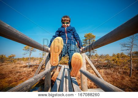 Cute little boy walking on trail in swamp and having fun, Kemeri national park, Latvia