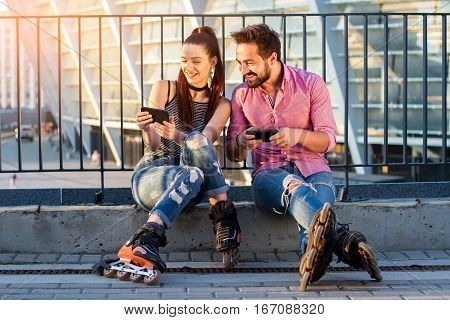 Smiling couple with cell phones. Two rollerbladers are sitting. Looking through our new photos.