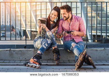 Man and woman with phones. Girl on inline skates smiling. Posting photos on the internet.